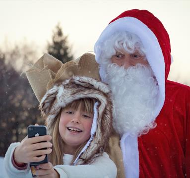 Father Christmas taking selfie with a girl