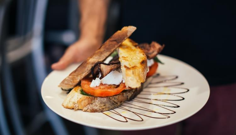 Crop man demonstrating plate of appetizing grilled sandwich in restaurant