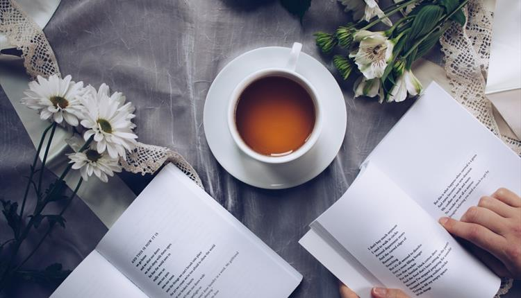 Poetry book, flowers and a cup of tea