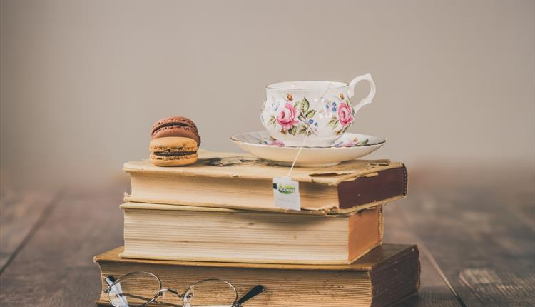 Stacked vintage books, glasses, cup of tea and macaroons