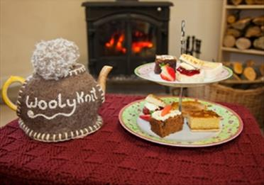 Cakes and tea pot with knitted wooley t cosy