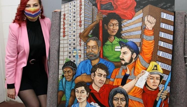 Woman standing next to a painting called 'The Frontline'