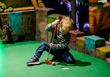 Child playing minigolf at Treetop Adventure Golf