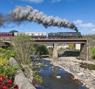 East Lancashire Railway train travelling over countryside bridge