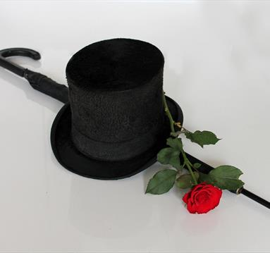 A top hat, red rose and umbrella