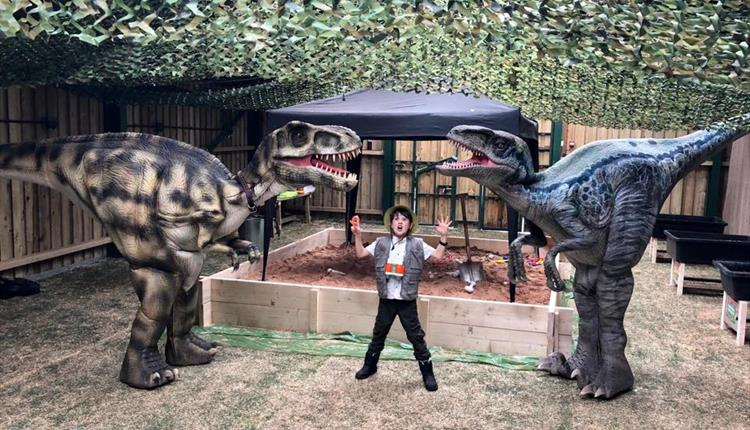 Child next to two dinosaurs