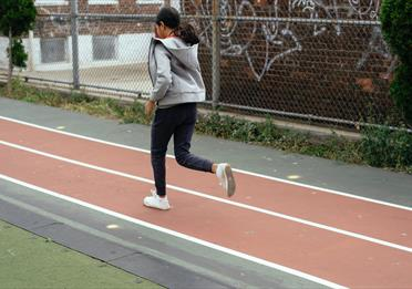 girl jogging on sports ground