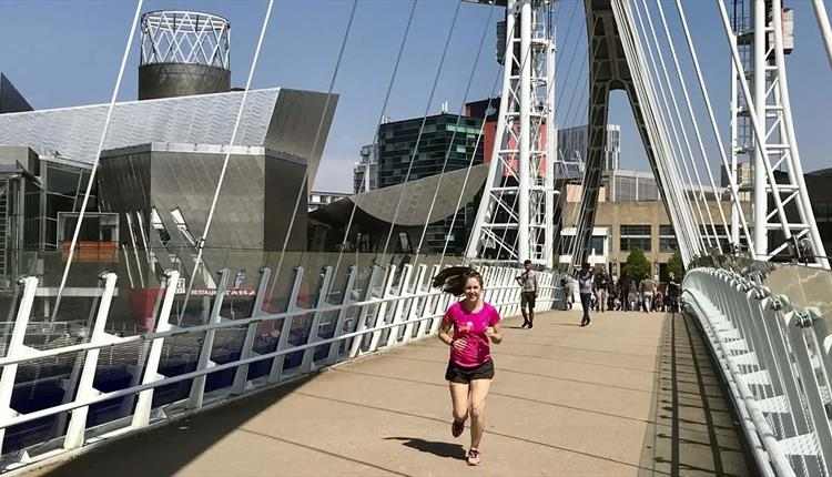 Woman in pink shirt running in Media City