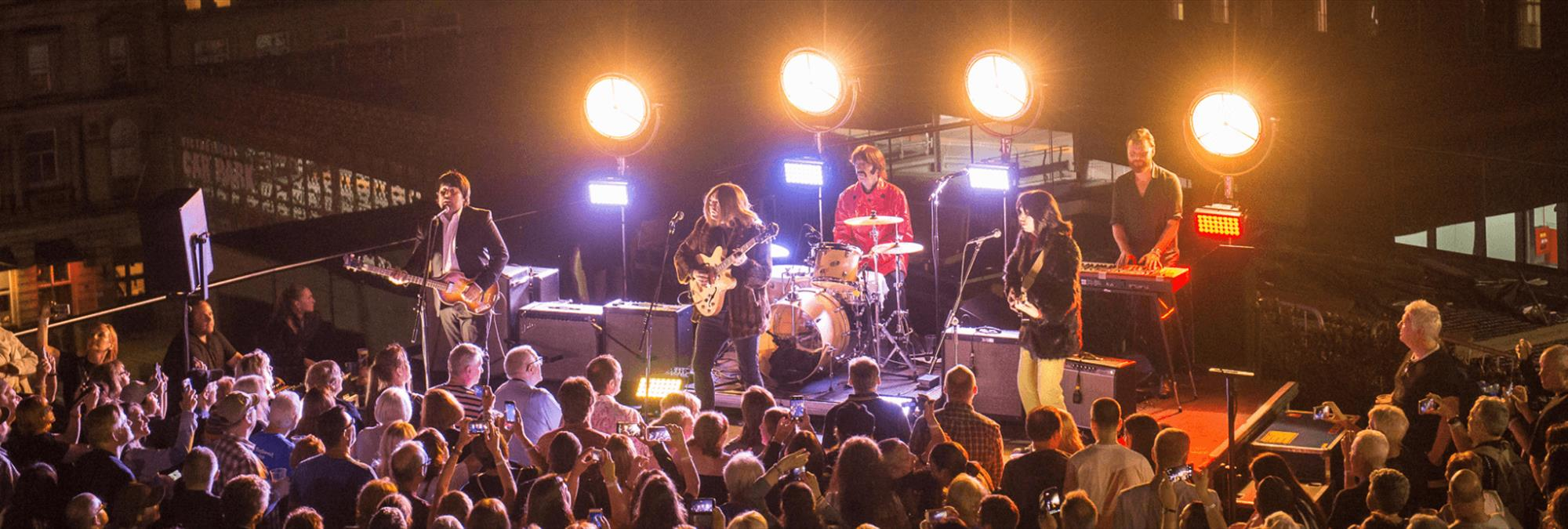 A band performing on the roof at night time.