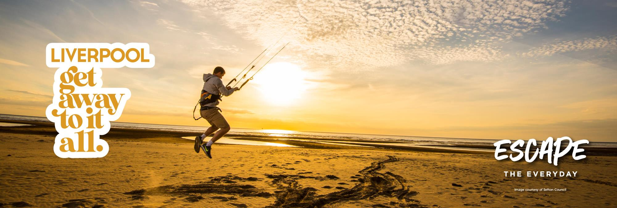 A man is about to paraglide on Crosby Beach at sunset.
