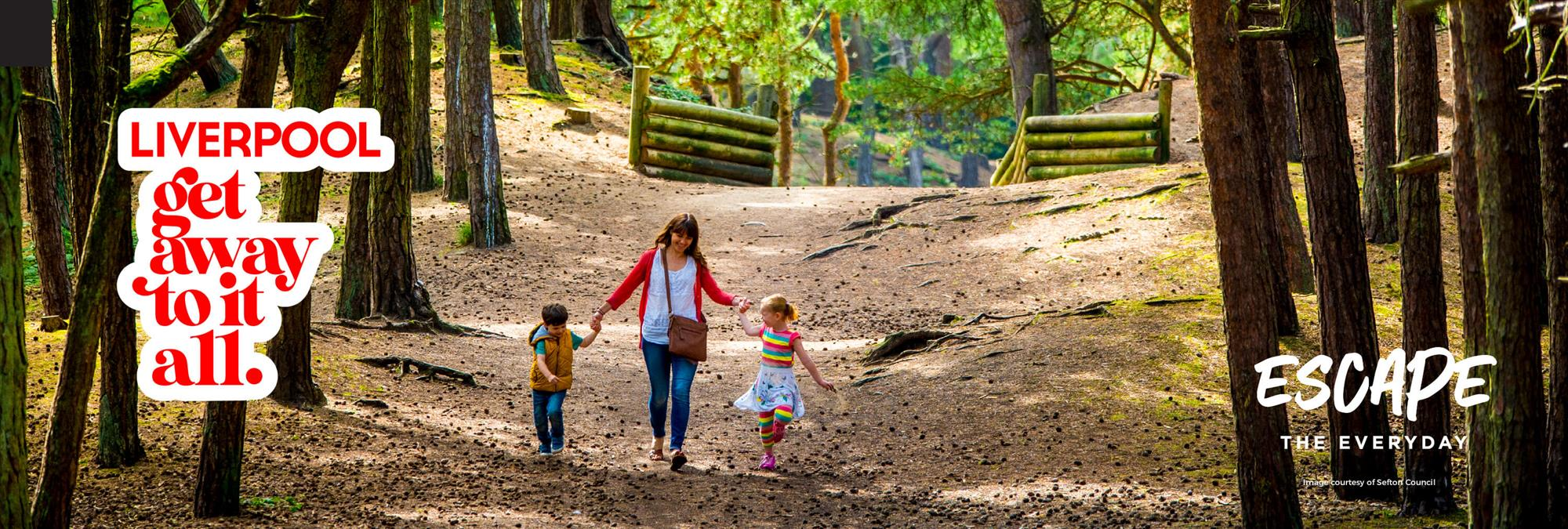 A family of one adult and two children walk through the Formby Woodland in the sun. They are holding hands and smiling.