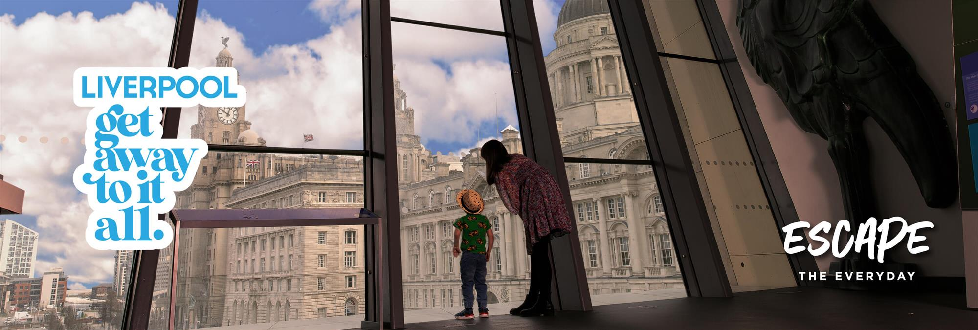 A guardian and child look out from the large window in the Museum of Liverpool over to the Pier Head and the grand Three Graces buildings.