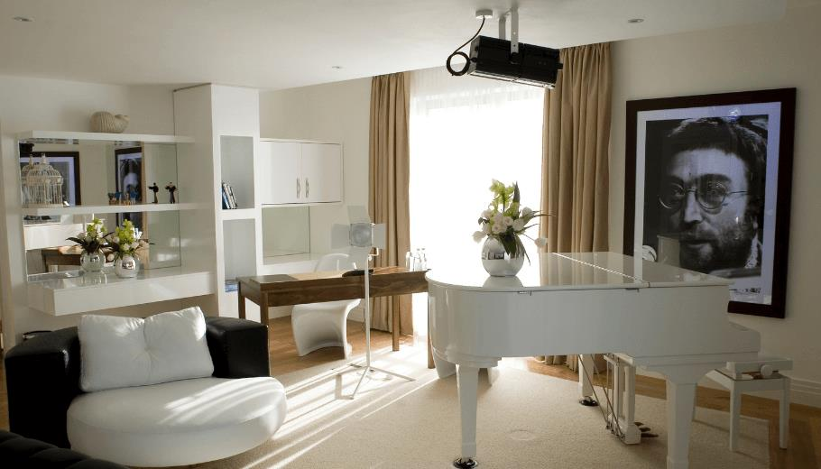 The Lennon Suite inside the Hard Days Night Hotel has plush cream tones, a large white grand piano and a black and white portrait of John Lennon on the wall.