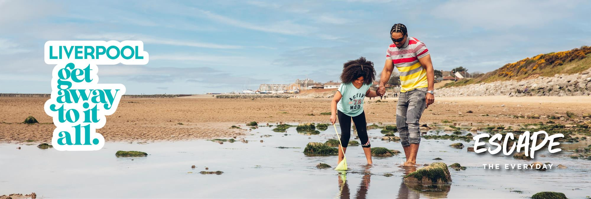 A child and older guardian fish around the little rock pools on the beach in New Brighton.