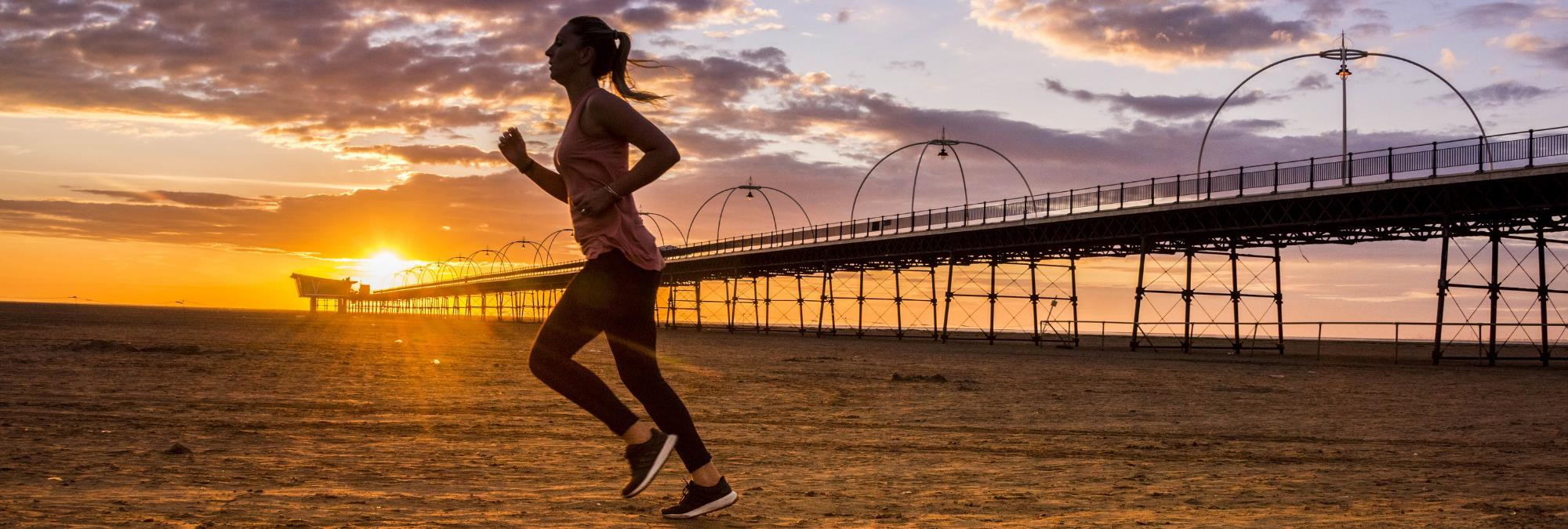 Southport Pier and Beach at Sunset. A lady is running along the beach with the orange sunset in the background.