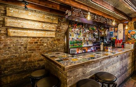 An entirely exposed brick dive bar, a small wooden bar in the corner with a patterned tile covered bar surface. Behind the bar are the traditional par