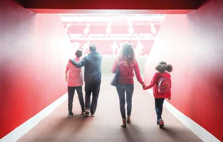 A family of four walking through the tunnel onto the pitch at Anfield.