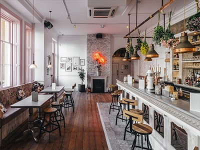 The downstairs bar area of the Florist is decorated light an airy with whites, light pink and browns.