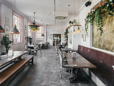 The upstairs dining area of the Florist complete with hanging flowers, copper pendant lights, white walls with pink detailing.