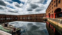 A daytime shot of the Royal Albert Dock. The shot shows the original warehouse buildings with the iconic red pillars.
