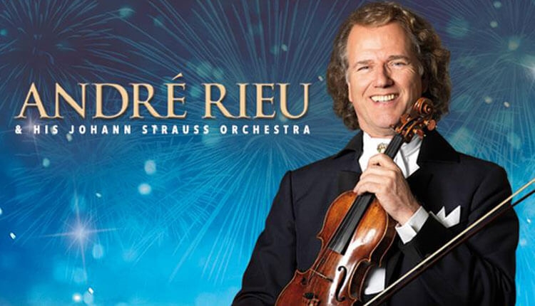 Andre Rieu holding a violin on a blue background.