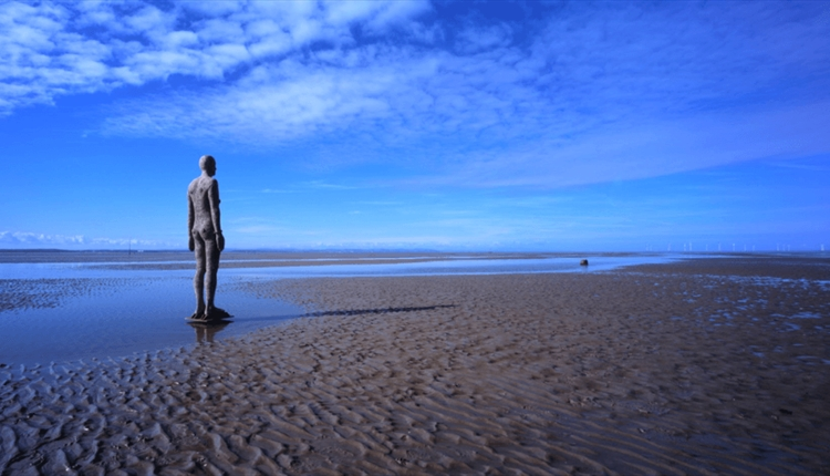 An image of the beach. The sky is blue and there is light cloud coverage. The tide is out and there is rope sand with puddles which are reflecting the