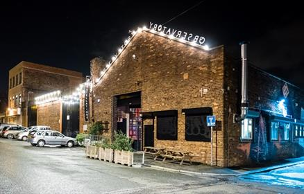 Constellations brick facade with bright lighting and up-cycled plantpots