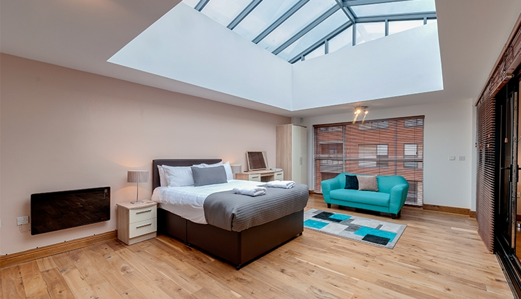 Open plan apartment with a glass roof, large bed and couch