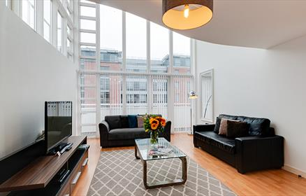 Living room space in city centre apartment showing huge windows