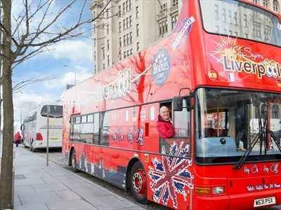 A large, open-top, red doubled-decker bus is parked on Liverpool's Pier Head. The driver in a red coat is leaning out of the driver window smiling.
