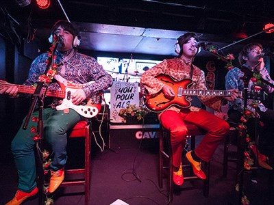 International Beatleweek celebrates everything Beatles in Liverpool. Image shows two men dressed in Beatles esc clothes playing guitar on stools