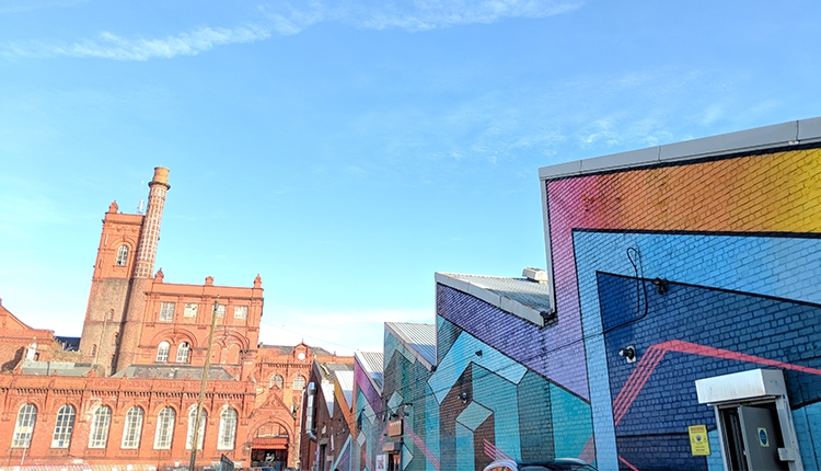 Cains Brewery Village From Outside. On the right is a jagged shaped building covered in colourful artwork. The red brick brewery building can be seen