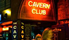 The exterior and entrance of the Cavern Club. The neon red entry sign reads 'Cavern Club.' There are two women leaving the club sminling.