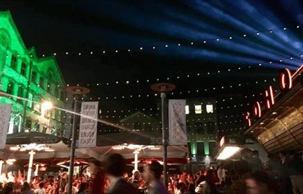 Busy nightlife scene with lasers and festoon lighting