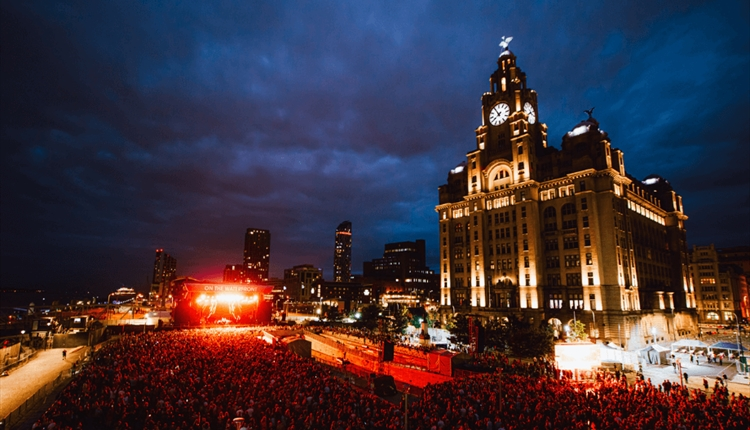 A night time shot of the crowds on the Pier Head at Cream Classical 2021. The Liver building is lit up to the right of the shot. On the left you can s