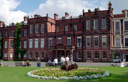 Outside of Croxteth Hall with people sitting on the grass, on benches and in a group talking in front of a round flower bed.