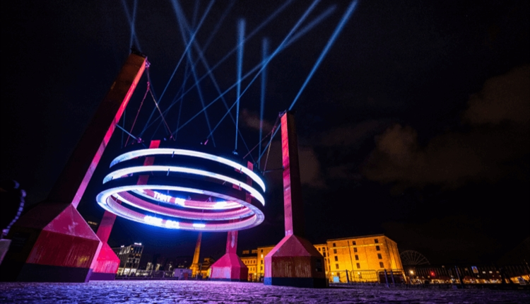 Large silver rings suspended on red ballasts with lights reflected in the sky.