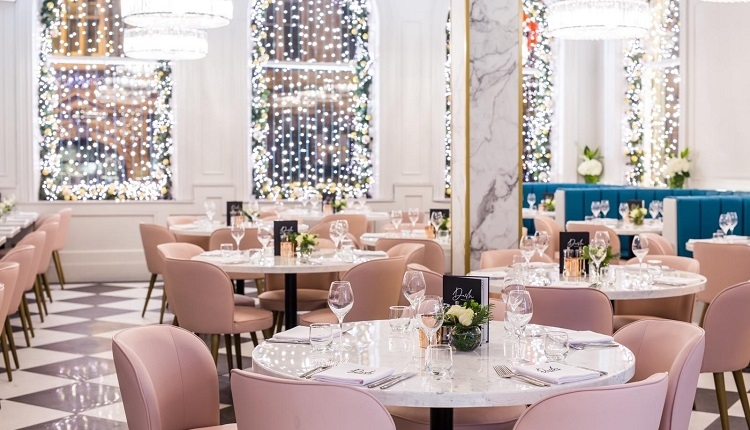Dash Restaurant and Bar. Blush pink seats amongst white rose flowers and chequered black and white floor and twinkling fairy lights.