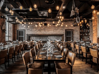 Fazenda main restaurant seating area. It is decorated in dark browns and leather tones. There are details relating to meat decorated throughout the ro