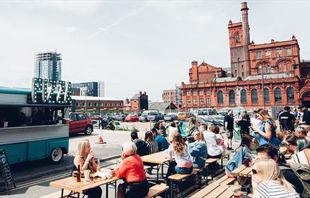 Crowds drinking outside Hinterlands in Cains Brewery Village