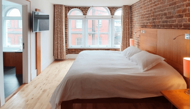 A King Sized bed with plush white bedding inside a large, bright hotel room. The walls are exposed brick and the floor is a light oak.