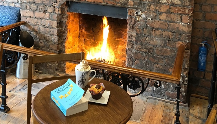 A roaring fire sits in an authentic, exposed-brick fire pit alcove. There are safety railings around the fire. In front of the fire sits a round table