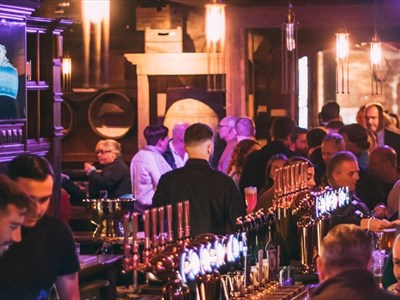 A traditional pub is bathed in purple lighting. There are a number of beer taps on the bar. The walls are traditionally cladded.