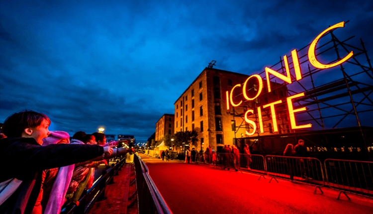 The words 'Iconic Site' in neon red lights is suspended on scaffolding in front of the Royal Albert Dock building which has been regenerated.
