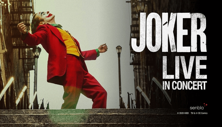 An iconic shot from the film 'The Joker' where the green haired character with clown face paint, yellow waistcoat and red suit dances on concrete step