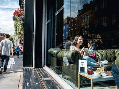 Looking through the large cafe windows. A girl sits on a green Chesterfield style couch