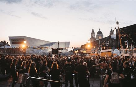 Liverpool's Waterfront at LightNight with a crowd of people watching a performance.