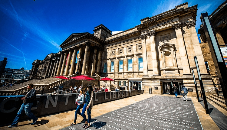 Outside of Liverpool Central Library featuring the tiled floor with the names of famous books on.