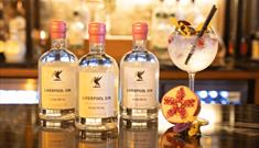 Three bottles of the Rose Petal Liverpool Gin next to a balloon glass filled with flowers, ice and gin!