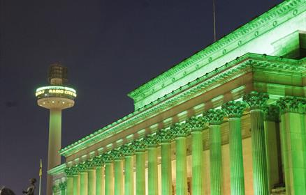St George's Hall a neo classical building with a number of pillars, bathed in green light.